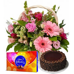 Enticing Chocolate Cake with Seasonal Flowers Basket and Cadbury Celebrations